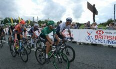 Cyclists seen in front of a sign for British Cycling, the boss of the governing body has recently condemned homophobia and transphobia in the sport