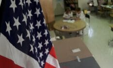American flag hangs in the foreground of a classroom as two people sit at a table in the background