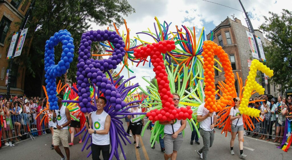 Revellers hold a Chicago Pride balloon display