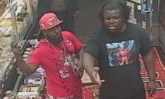 Two men, one wearing red and the other black, stand in a shop