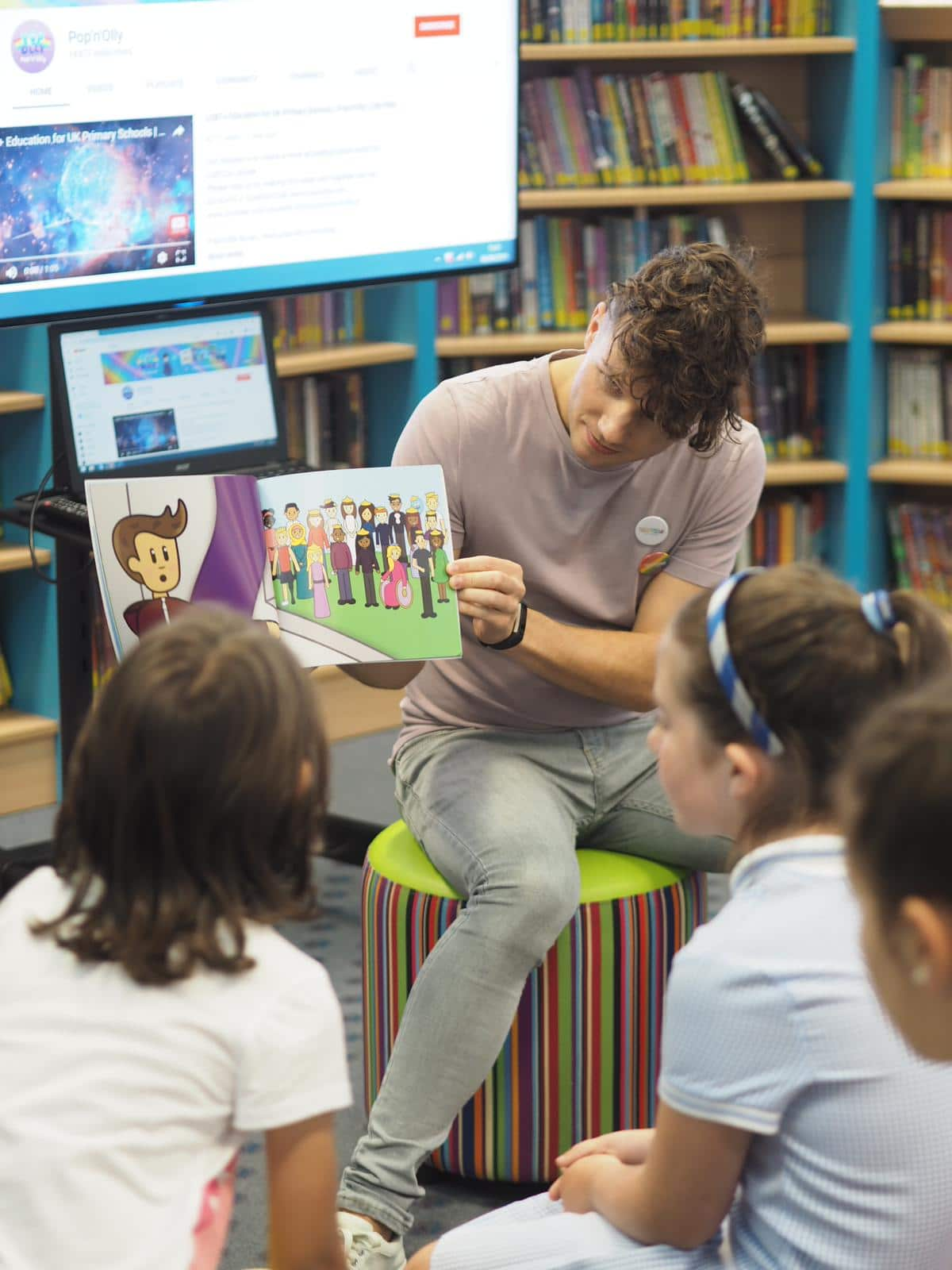 Olly Pike reading a picture book to children