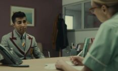 Anwar, a character from Netflix's Sex Education, sits across from a nurse at a sexual health clinic who gives him a lesson about HIV