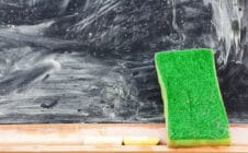 An eraser against a blackboard covered in smeared chalk