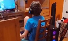A 12-year-old sits on a wooden chair playing video games