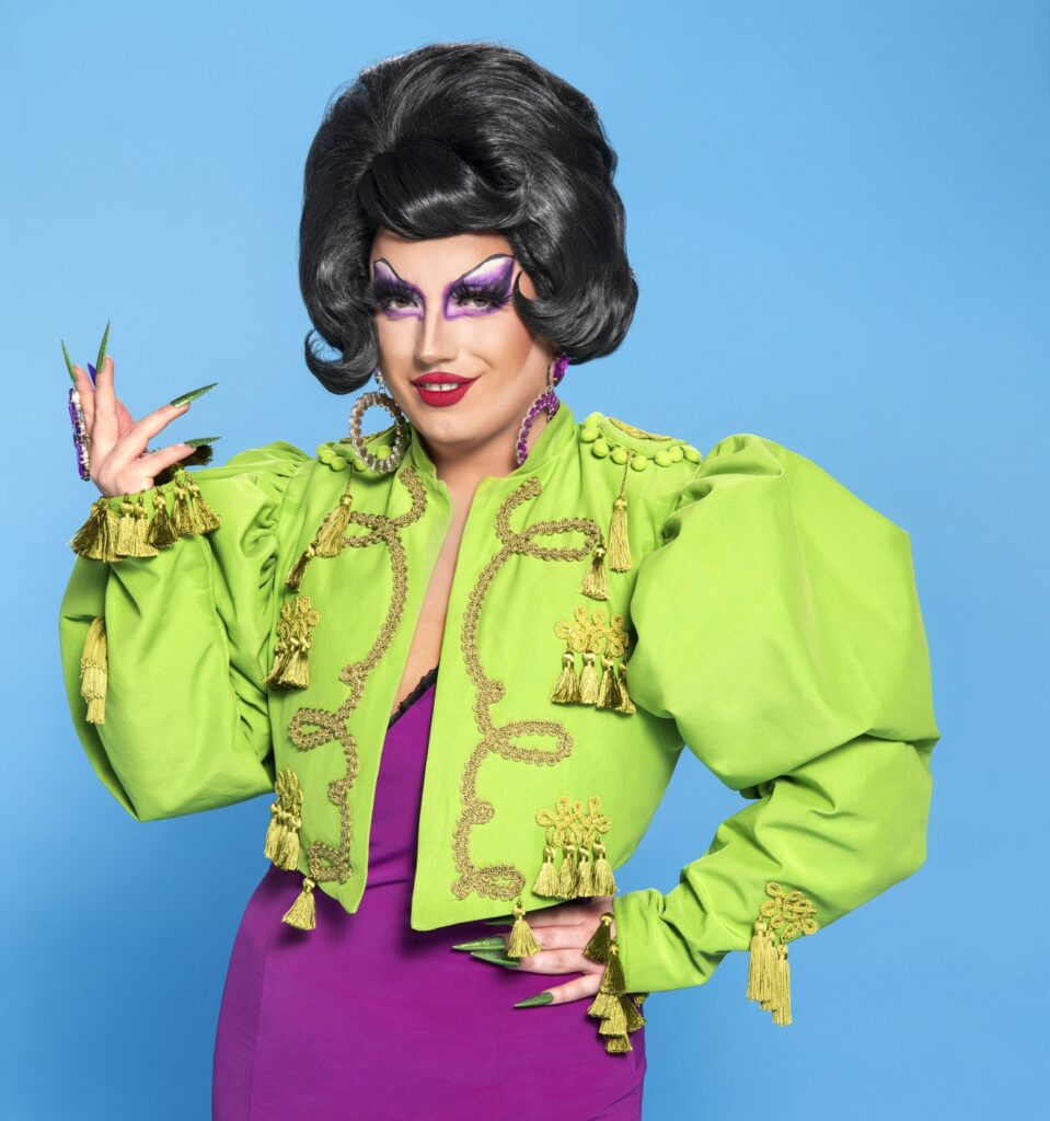 Drag Race UK queen Choriza May in a pruple dress with green jacket
