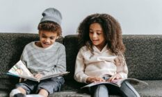 Two children are sitting on a couch and reading books