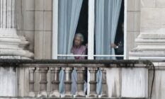 The Queen looking out of her window at Buckingham Palace.