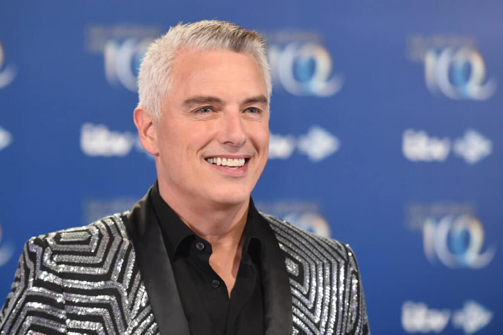 John Barrowman in a glitzy silver and black suit, smiling