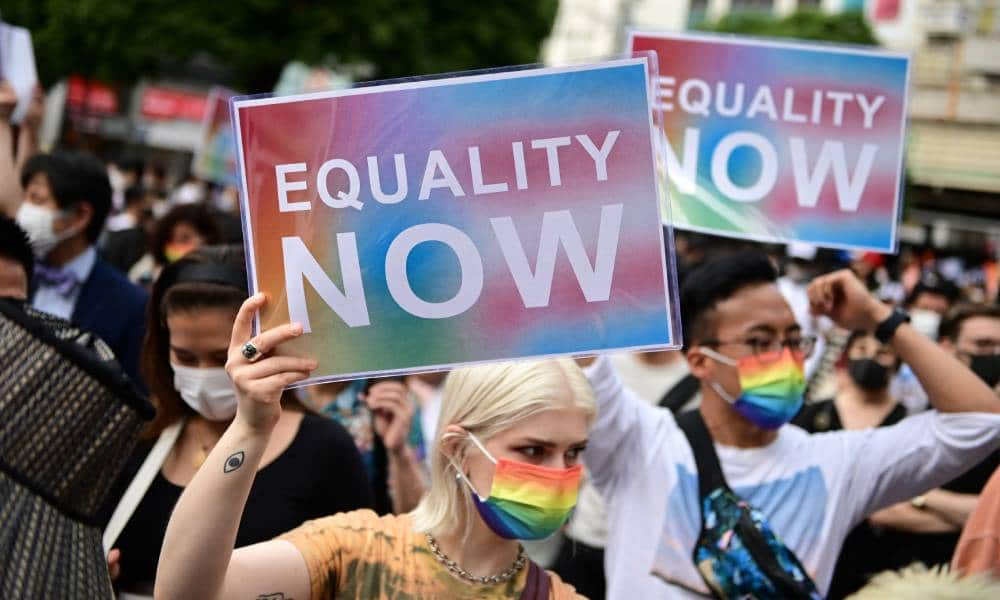 People hold up signs reading 'equality now' during a rally organised by an activist group in support of LGBT+ legislation in Shibuya district of Tokyo, Japan