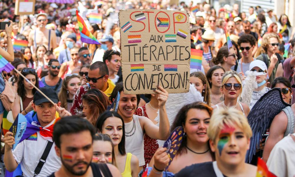 A Pride March participant holds up a sign written in French that calls for the end of conversion therapies