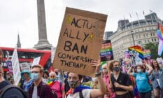 """A protestor holds a placard that reads """"actually ban conversion therapy"""""""