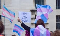 A protester wrapped in a trans Pride flag holds a 'Never Stop Fighting' placard during the trans rights demonstration
