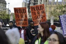 Protesters buttress placards up high standing in solidarity with queer refugees in Parliament Square