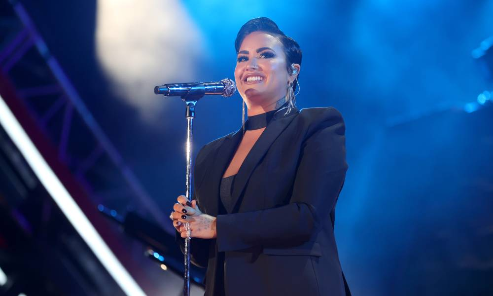 Demi Lovato performs during Global Citizen Live in a black outfit in front of a blue background