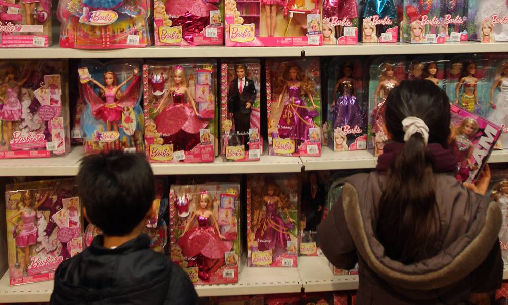 Children look at Barbie dolls in a toy store