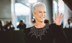 Jamie Lee Curtis waves at the crowds in a black dress with a collar designed to look like spider web