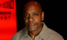 Dave Chappelle wears a neutral coloured shirt amid a black and red background