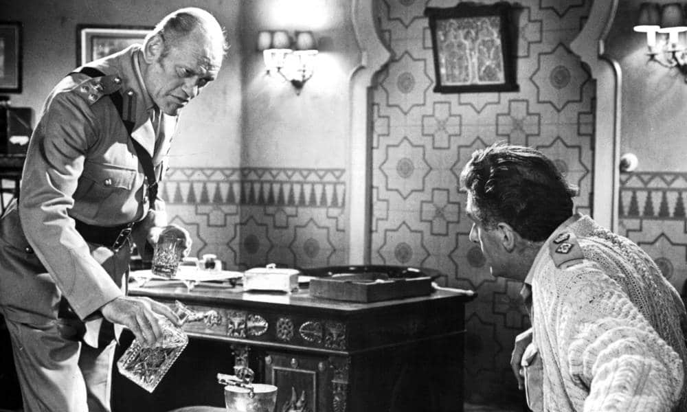 Harry Andrews with a carafe in one hand and a glass in the other in a scene from the film 'Play Dirty'