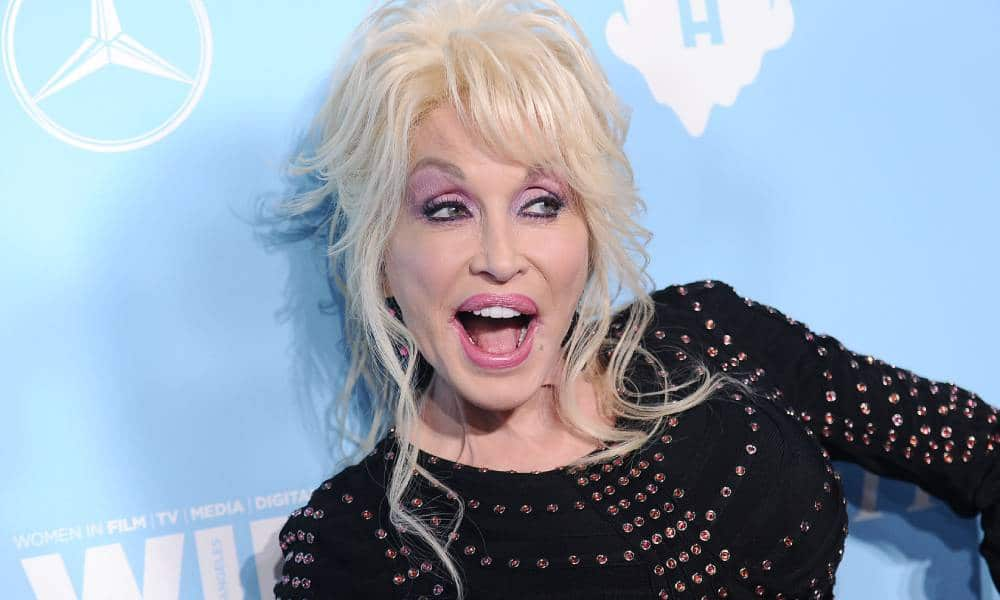 Colly Parton is dressed in black amid a light blue background at Variety and Women in Film's 2017 pre-Emmy celebration