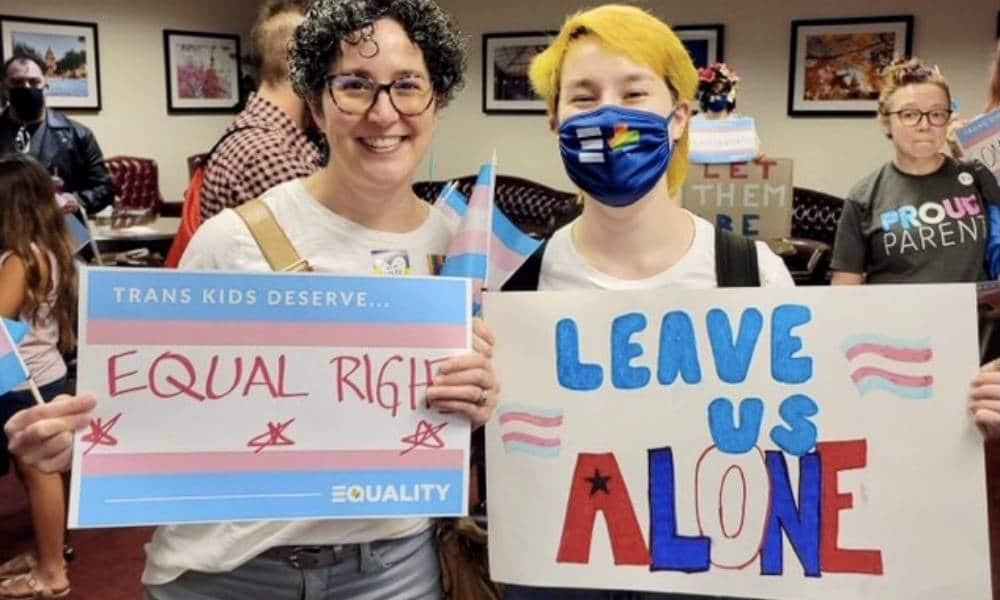 Mandy Giles and Indigo attend a trans rights protest in Texas. Mandy holds up a sign calling for equal rights for trans people while Indigo holds up a right that reads 'leave us alone'