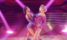 A still image of JoJo Siwa and Jenna Johnson from Dancing With the Stars where they dance amid pink and blue lighting
