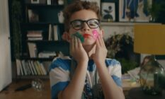 still from the latest John Lewis home insurance ad. The still depicts a young boy wearing a dress and colourful makeup smearing paint on his face