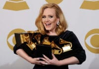 Adele holding an armful of Grammys