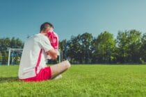 Man sitting on a football pitch crying