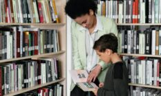 A person helps a child look at a book in a library setting