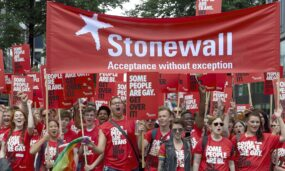 Protesters holding placards saying 'some poeple are gay/bi/trans, get over it'